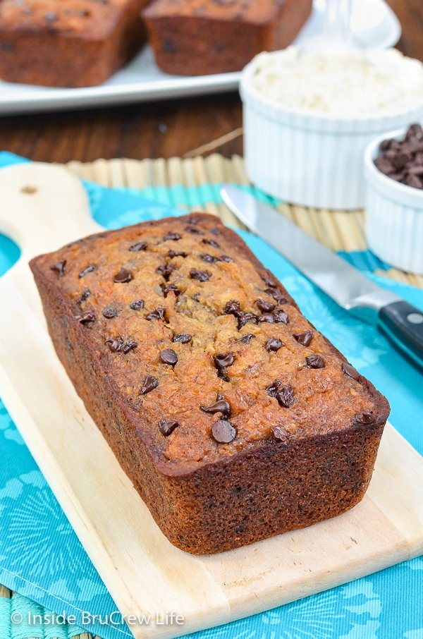 A loaf of healthy skinny banana bread with chocolate chips on a light brown cutting board and more loaves behind it.
