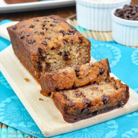 A cutting board with a loaf of healthy chocolate chip banana bread with a few slices falling down in front of it.
