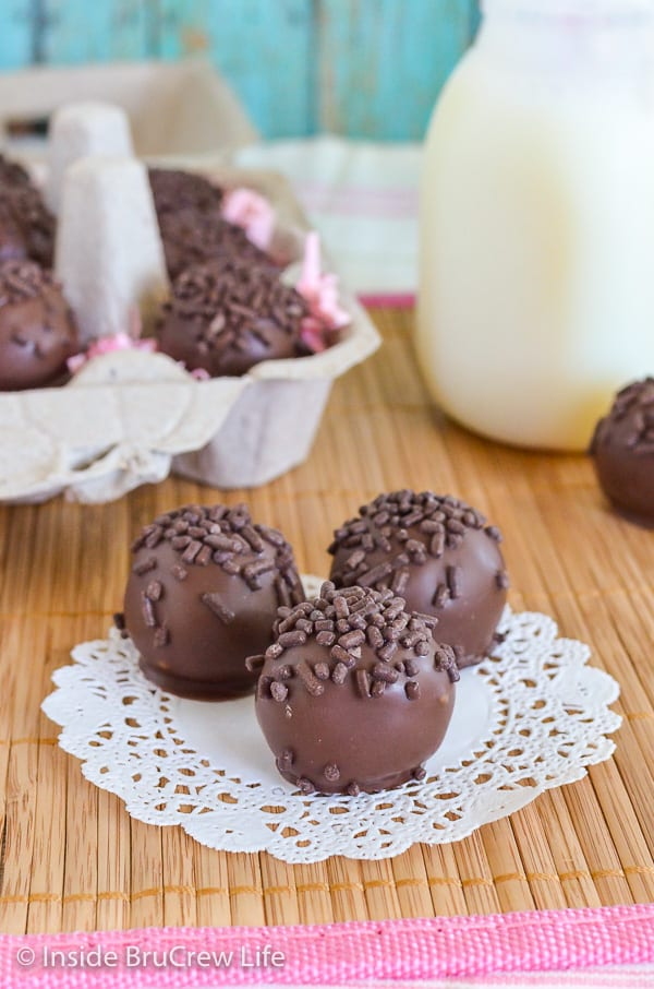 Three chocolate covered butterfinger cookie dough bites topped with chocolate sprinkles on a white doily