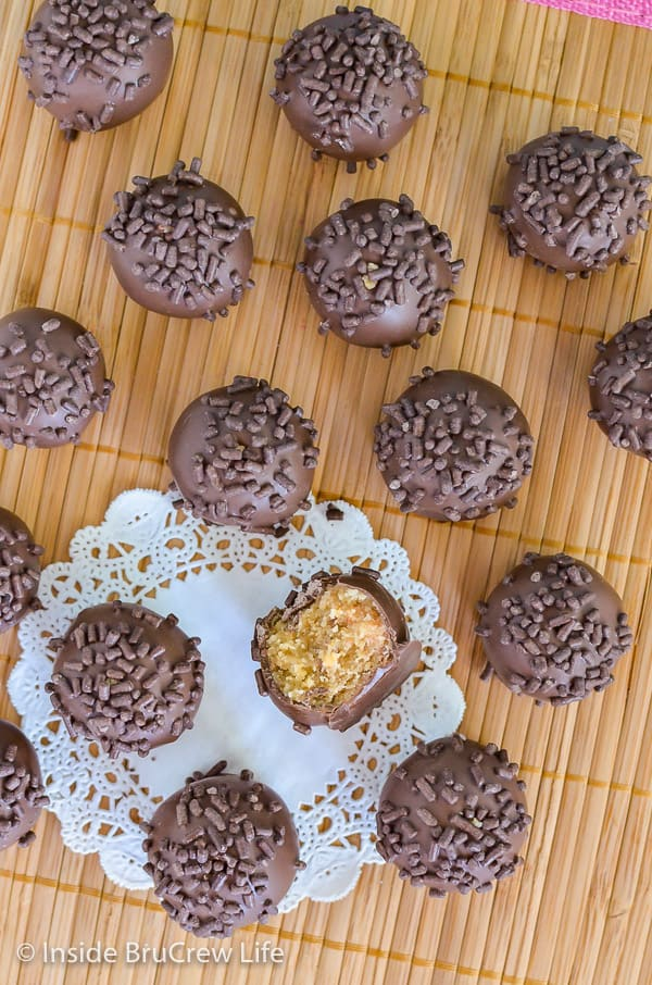 An overhead picture of butterfinger cookie dough truffles with chocolate sprinkles on top on a yellow wood placemat