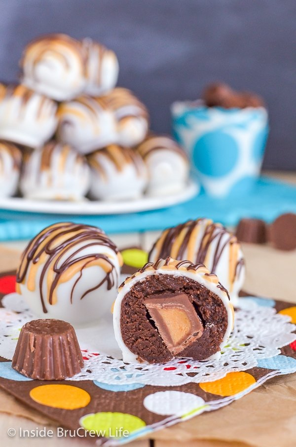 Three chocolate cookie dough truffles on a white doily with one cut in half to show a hidden peanut butter cup