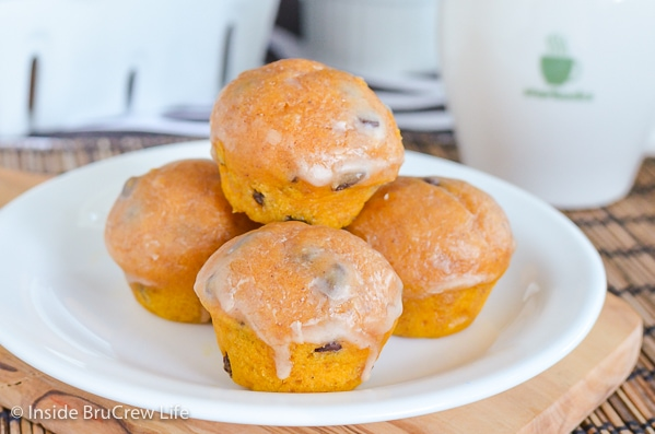 A white plate with glazed mini chocolate chip pumpkin muffins on it.