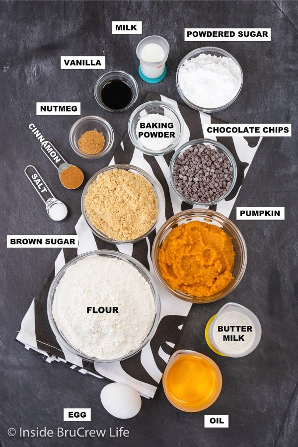 A dark board with bowls of ingredients needed to make mini pumpkin muffins with chocolate chips.