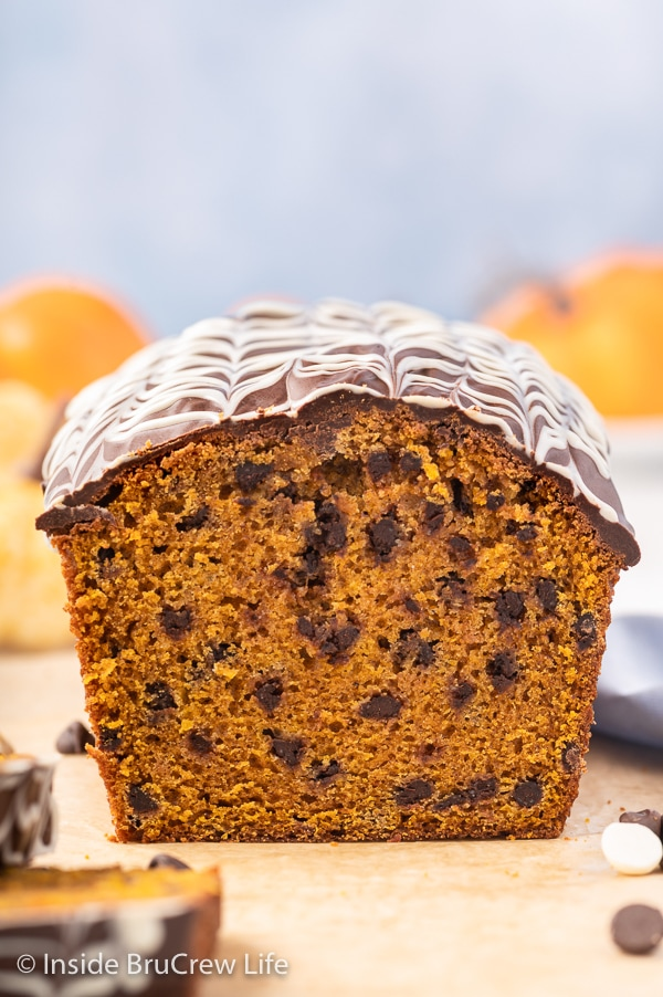 A loaf of pumpkin chocolate chip bread topped with chocolate drizzles on a wooden cutting board.