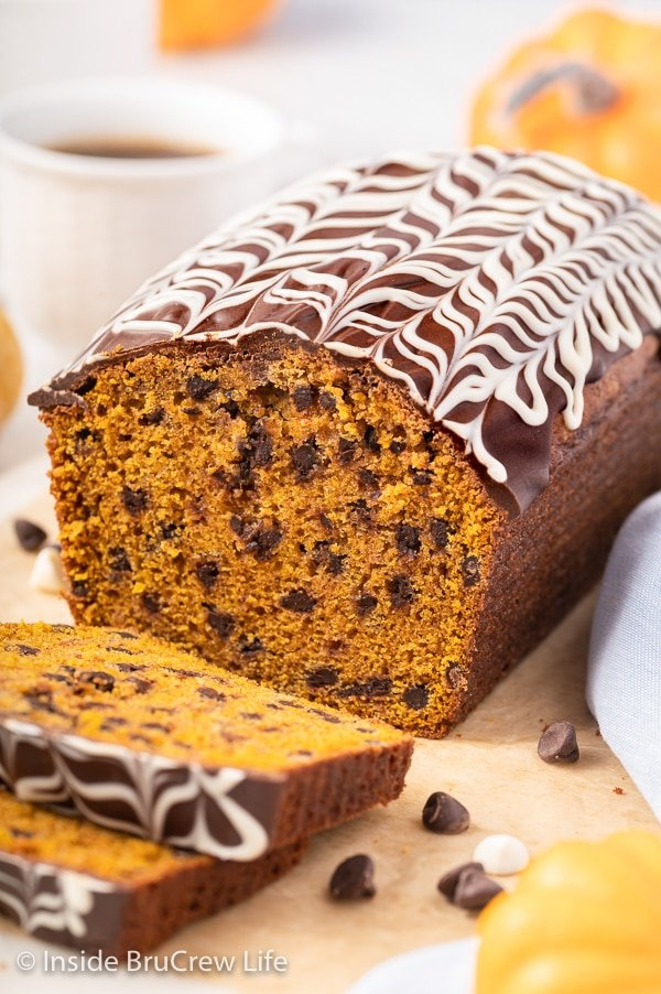 A loaf of chocolate chip pumpkin bread topped with a chocolate drizzle.