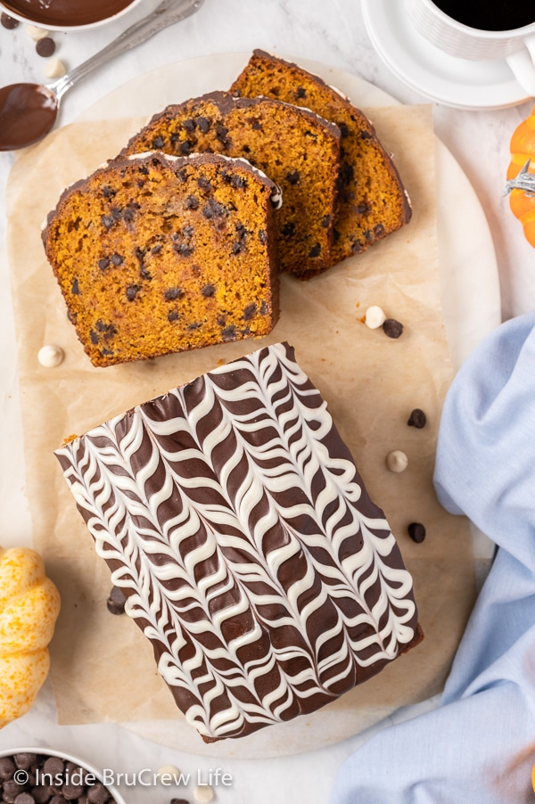 Overhead picture of a loaf of pumpkin bread topped with pretty chocolate drizzles.