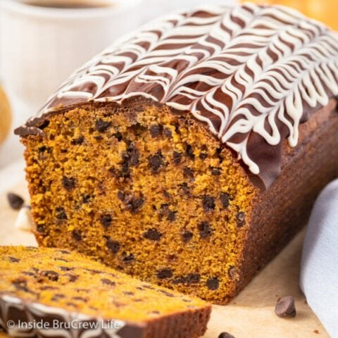 A loaf of pumpkin chocolate chip bread on a wooden board.