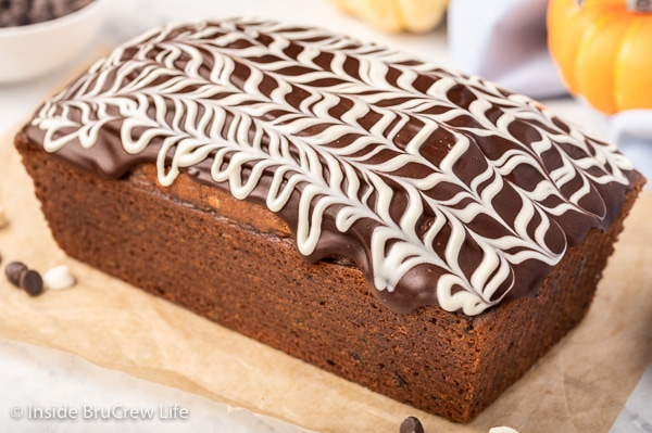A loaf of pumpkin bread on a tray topped with chocolate and white chocolate drizzles on top.