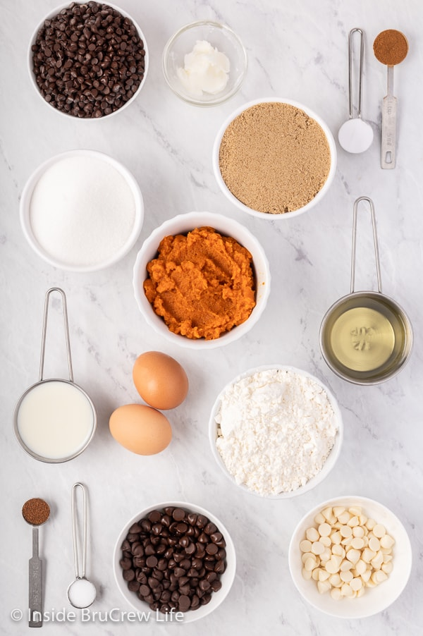 A white board with bowls of ingredients to make a pumpkin chocolate chip bread.