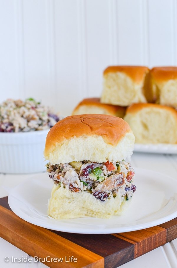 A roll filled with apple cranberry turkey salad sitting on a white plate with more rolls behind it