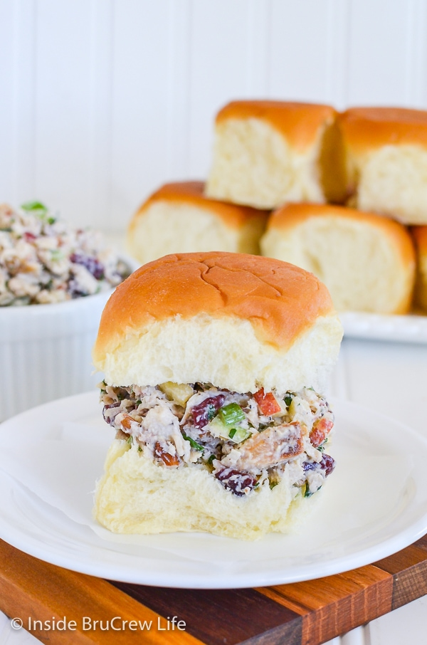 A roll filled with turkey salad on a white plate and more rolls behind it