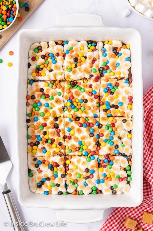 An overhead picture of a white pan with toasted marshmallow brownies topped with M&M candies.