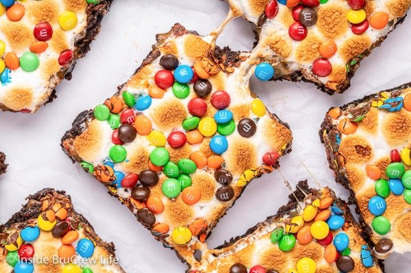 Gooey caramel marshmallow brownies topped with M&M's on a white board.