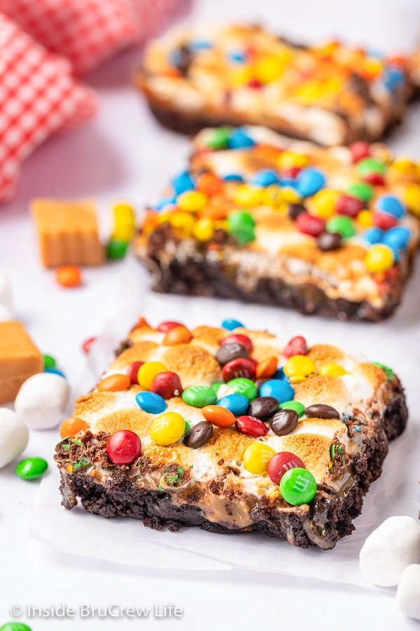 Three caramel marshmallow brownies topped with M&M's on a white board.