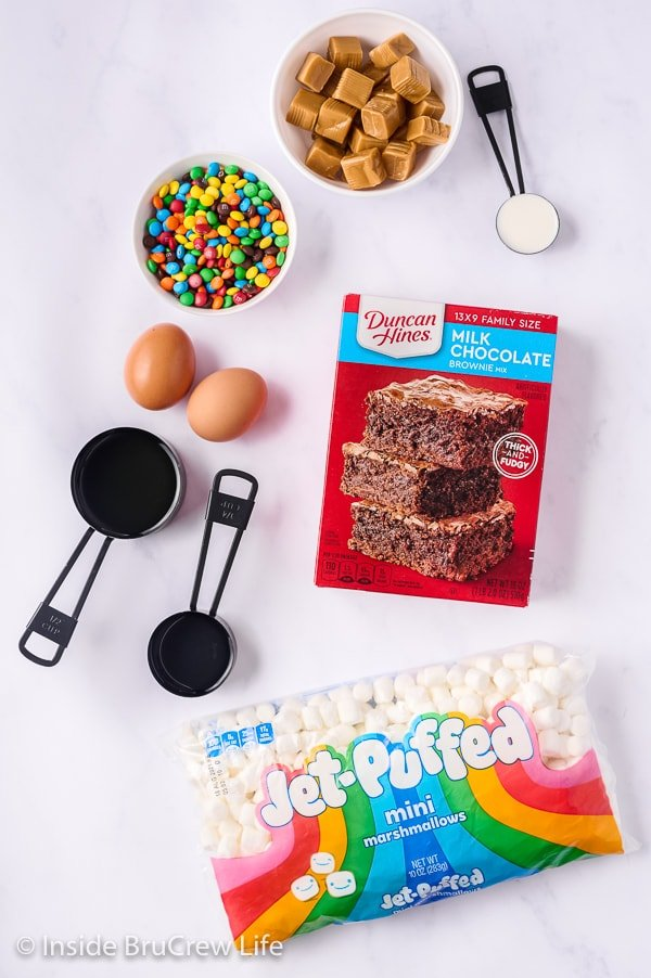 A white board with all the ingredients needed to make caramel marshmallow M&M brownies.