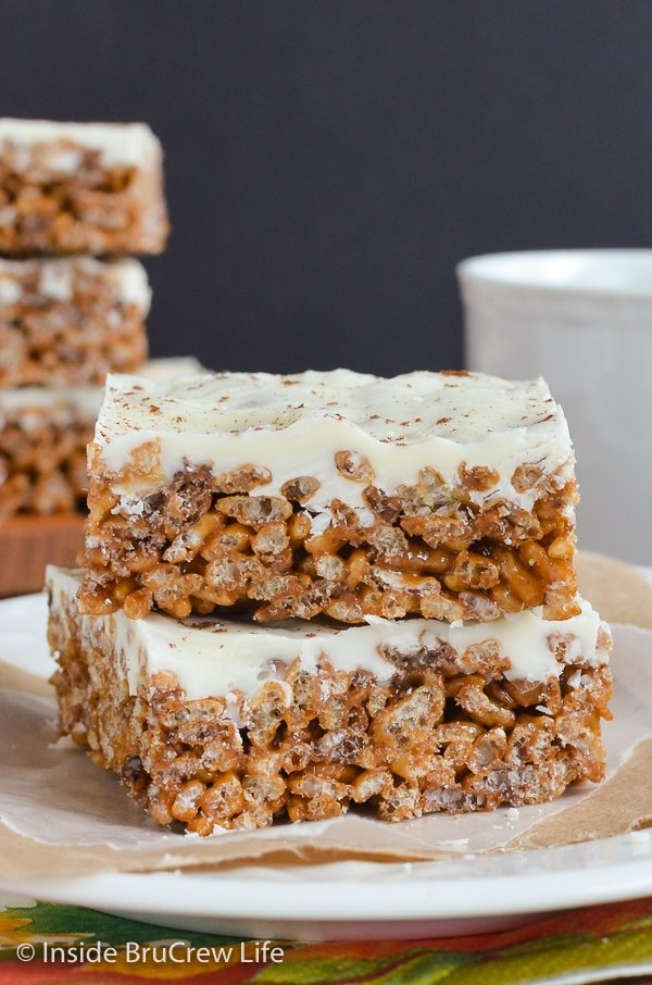 Two pumpkin spice treats topped with white chocolate stacked on a white plate.