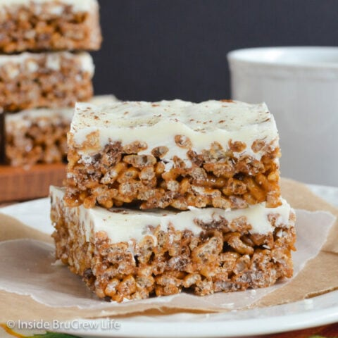 Two pumpkin spice rice krispie treats with white chocolate on a white plate.