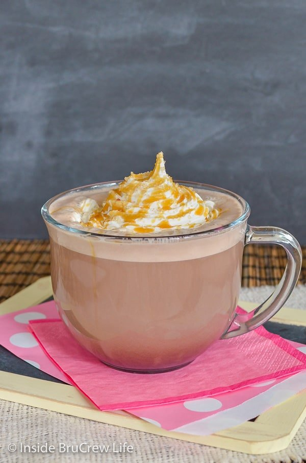 Clear glass mug filled with a homemade latte topped with Cool Whip and caramel drizzles