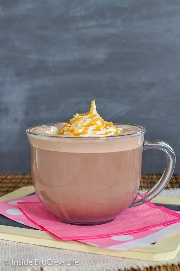 Clear mug filled with a homemade caramel latte and topped with Cool Whip with caramel drizzles and sea salt sprinkles