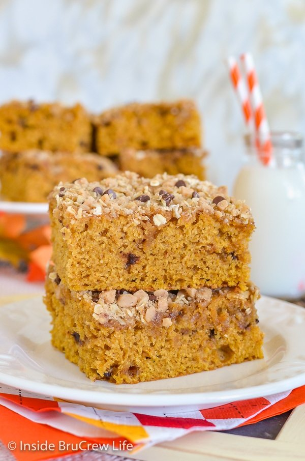 A white plate with two squares of pumpkin coffee cake with streusel stacked on it