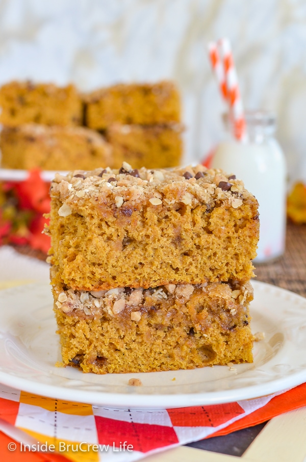 Two squares of pumpkin coffee cake with streusel stacked on a white plate