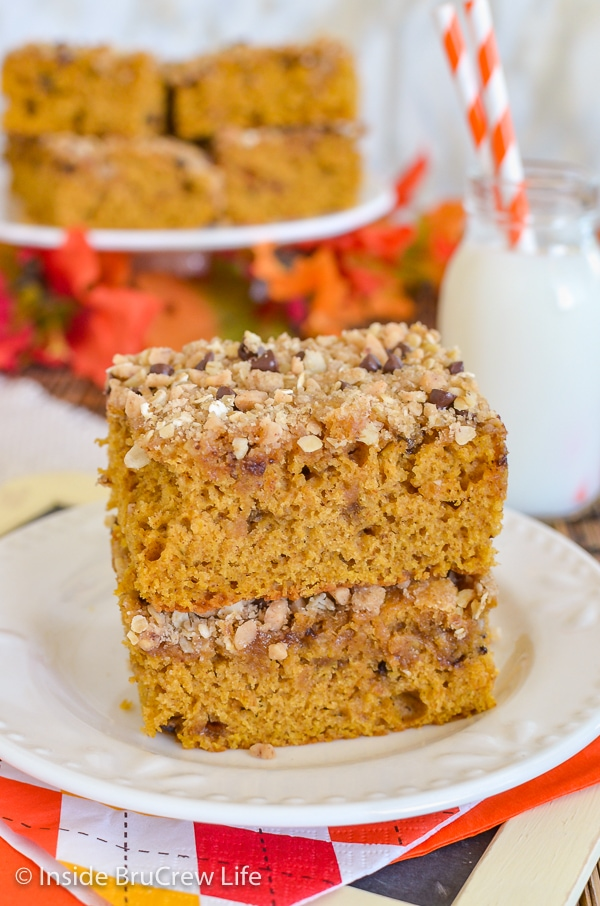 Two squares of pumpkin streusel coffee cake stacked on top of each other on a white plate