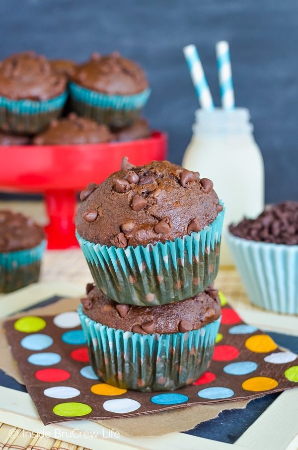 Two double chocolate banana muffins stacked on top of each other on a colorful napkin. More muffins and milk behind them.