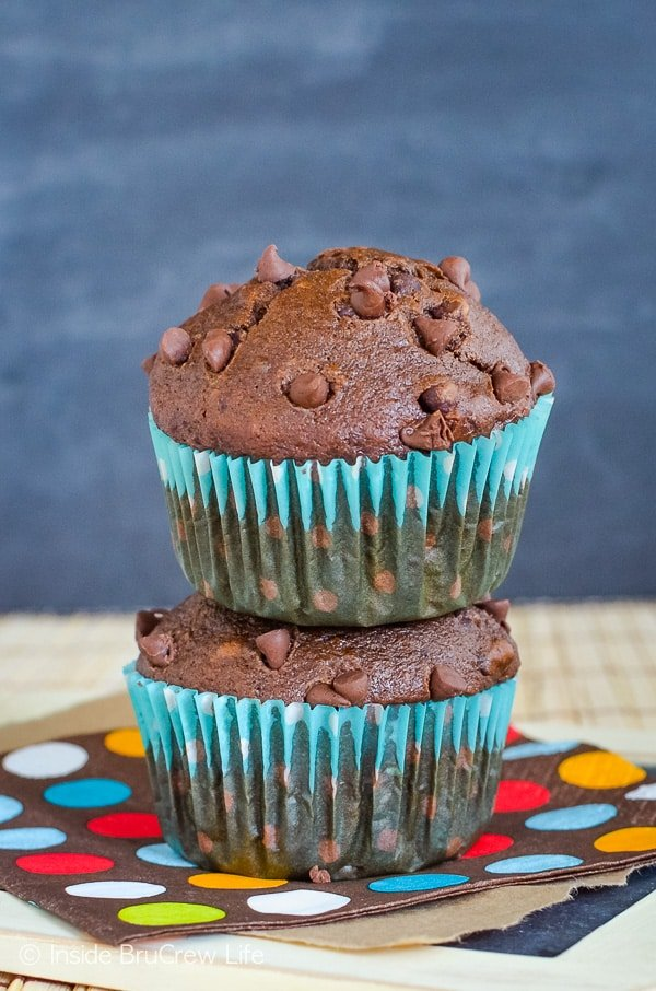 Two chocolate banana muffins in a teal muffin wrapper stacked on top of each other.