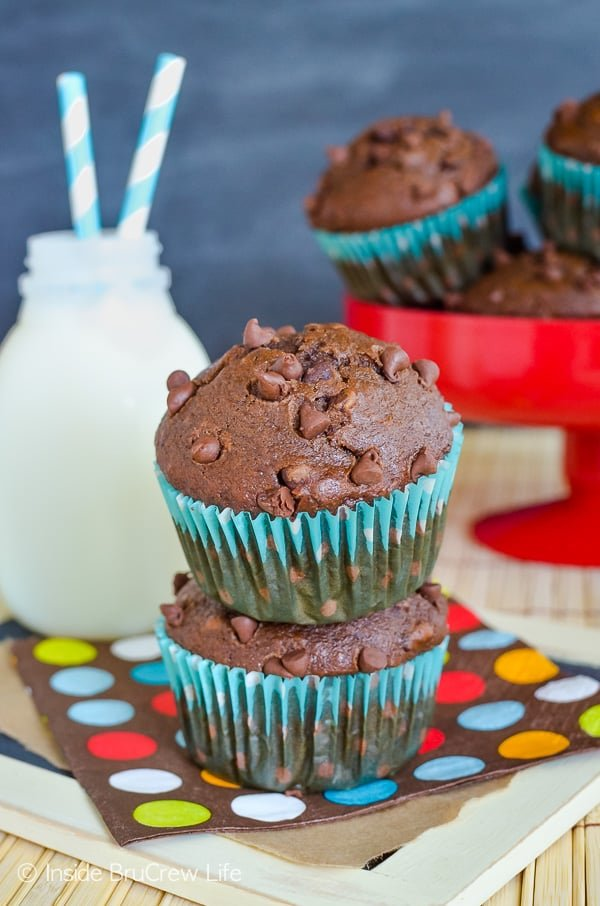 Two chocolate banana muffins with chocolate chips on a colorful napkin. A red plate with more muffins is behind them.