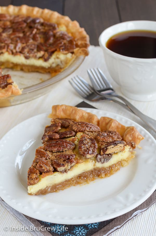 A slice of pecan cheesecake pie on a white plate with a cup of coffee behind it