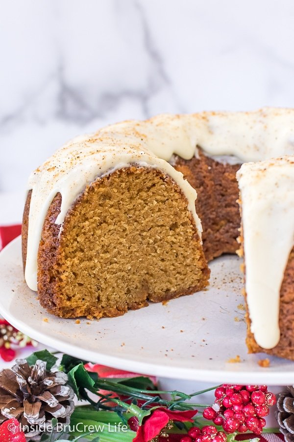A white cake plate with an eggnog bundt cake on it showing a slice missing