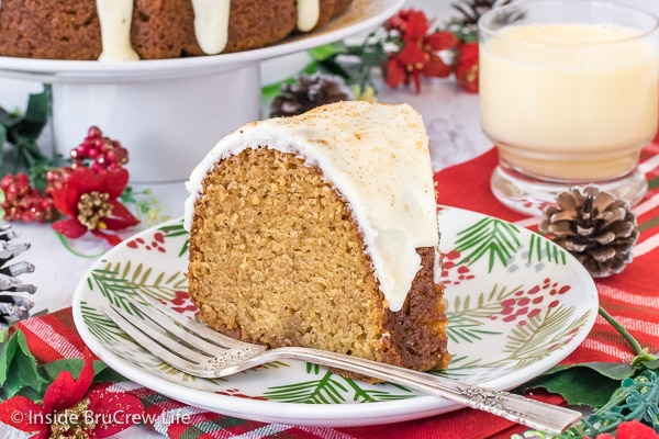 A white plate with a slice of eggnog bundt cake topped with eggnog glaze on it