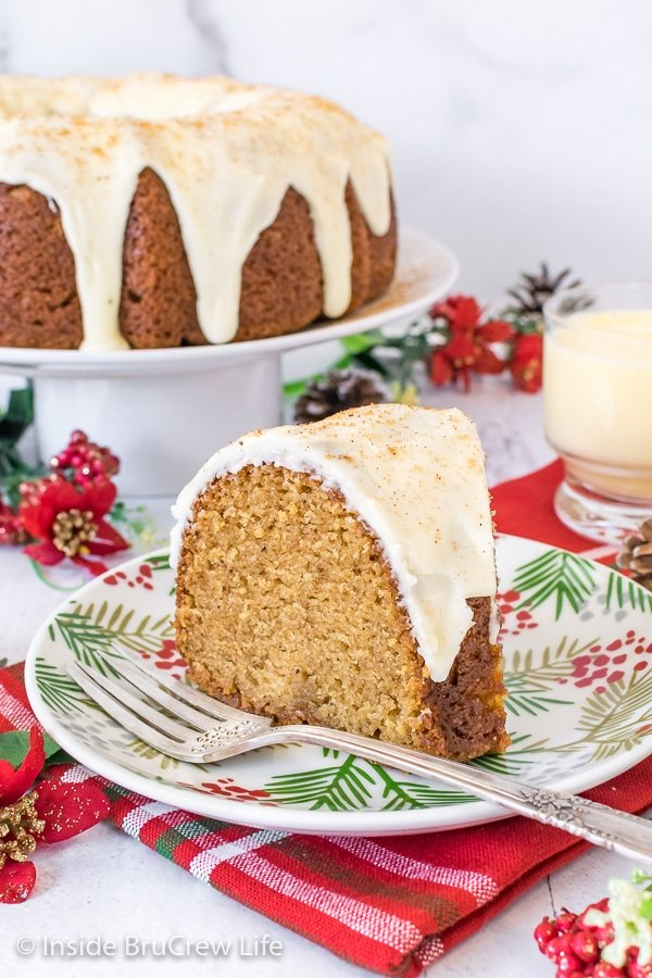 A white plate with a slice of eggnog bundt cake topped with eggnog glaze on it and more cake behind it