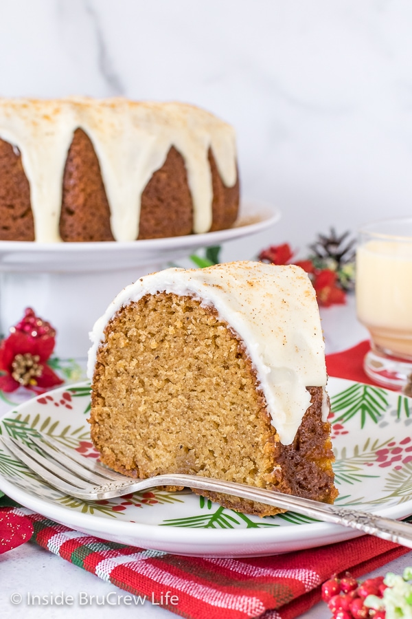 A slice of Eggnog Bundt Cake topped with eggnog glaze on a white plate with more cake on a cake plate behind it