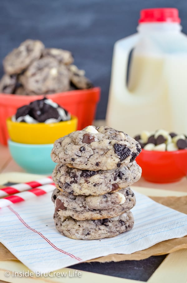 A stack of cookies and cream cookies on a white napkin with milk and more cookies behind it