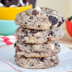 A stack of four chocolate chip cookies and cream cookies on a white napkin