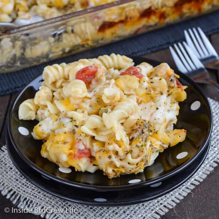A black plate with cheesy chicken pasta bake on it.