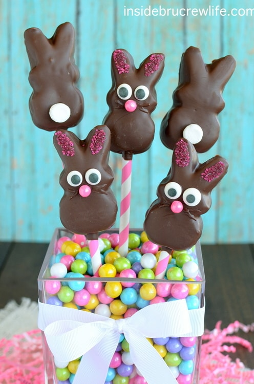 Chocolate Covered Marshmallow Bunnies on pink and white straws pushed in a jar of pastel candies