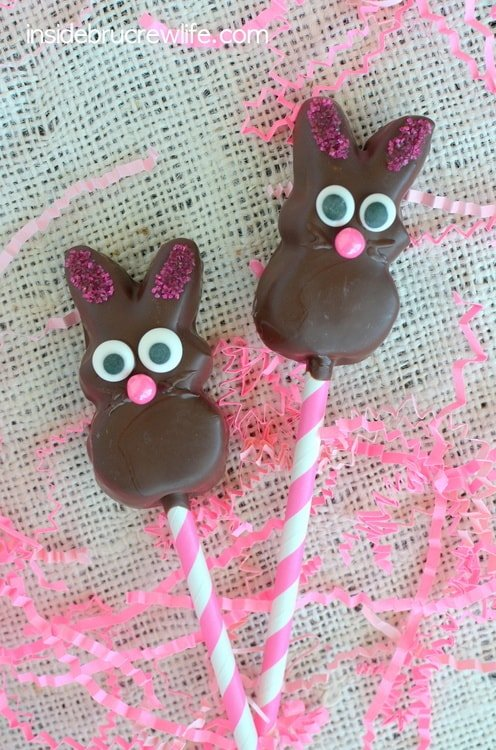 Two Chocolate Covered Marshmallow Bunnies on pink and white straws lying on a piece of cream burlap