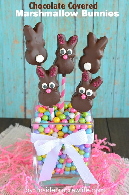 5 no bake Chocolate Covered Marshmallow Bunnies on straws in a vase full of pastel candies