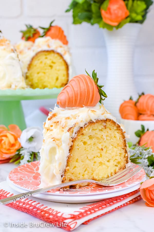 Coconut Cream Bundt Cake - this coconut Bundt Cake has three times the coconut baked into it. A cream cheese frosting and orange dipped strawberries add a fun flavor twist to the easy cake. Make this recipe for spring parties! #coconut #cake #bundtcake #cakemix #easter