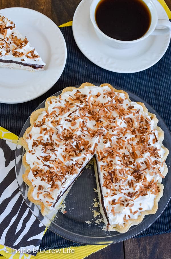 Overhead picture of a whole coconut cream chocolate pie with one slice out on a white plate behind it