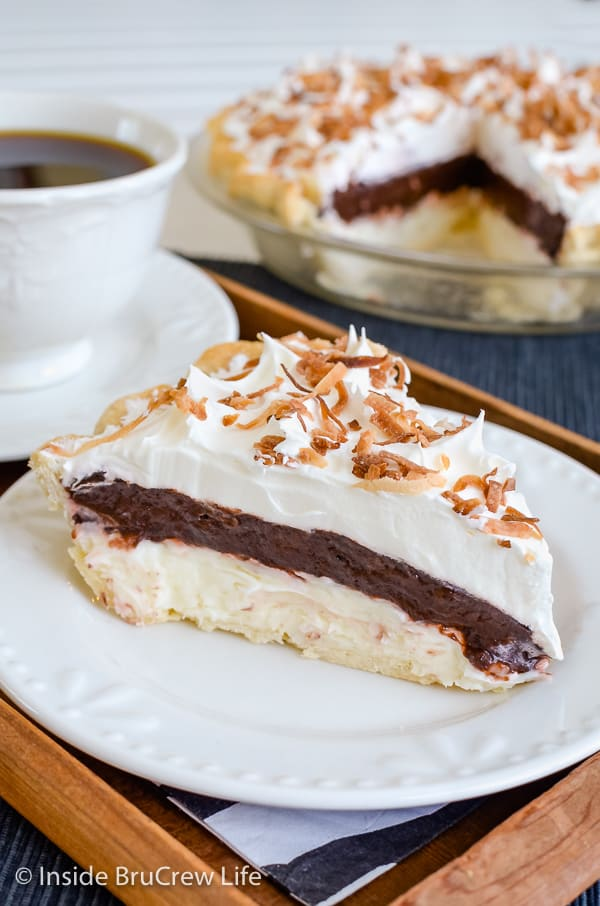 A white plate on a wood tray with a slice of coconut chocolate pie with cool whip and toasted coconut on it and pie plate behind it