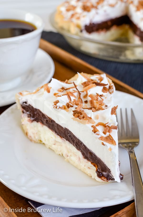 A white plate with a slice of coconut cream chocolate pudding pie topped with Cool Whip and toasted coconut and more pie behind it