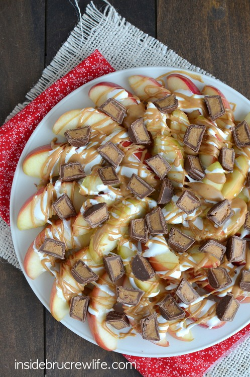 Apple slices covered in peanut butter, marshmallow, and peanut butter cups is a sweet treat.