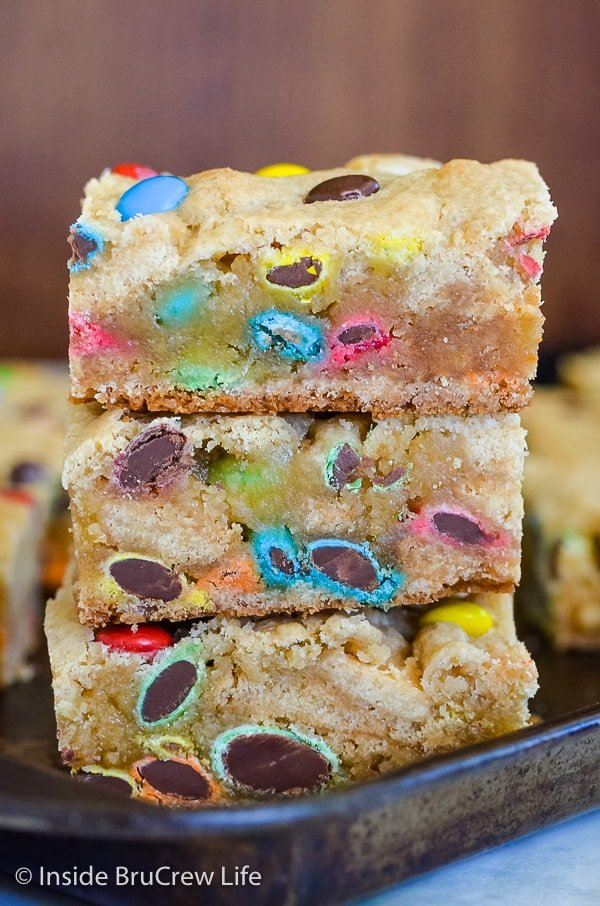 M&M Blonde Brownies - soft cookie bars loaded with lots of colorful candies makes this a favorite dessert recipe with everyone. Make a pan of cookie bars and watch them disappear! #blondebrownies #candy #easydessert #cookiebars #bakesaletreats