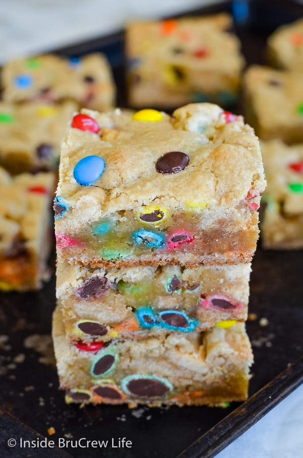 M&M Blonde Brownies - these sweet cookie bars are loaded with lots of colorful candies. Change out the colors for different holidays! Make this easy recipe and watch them disappear! #blondebrownies #candy #easydessert #cookiebars #bakesaletreats