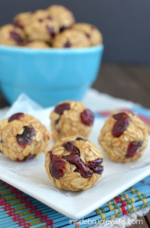 Four peanut butter cranberry granola bites on a white plate with a blue bowl full of bites behind it
