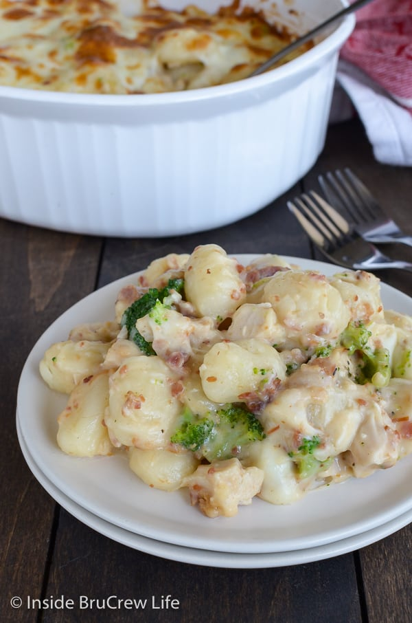 A white plate with chicken alfredo gnocchi on it and a white casserole dish behind it
