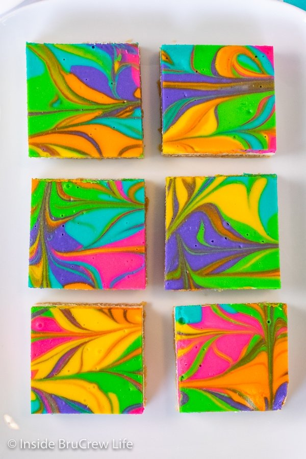 Overhead picture of six rainbow cheesecake bars on a white tray